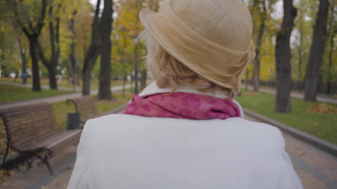 Back view of nice Caucasian woman in elegant beige cloche hat and white coat Footage