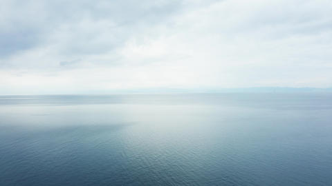 Drone flying over peacefull and calm open sea with blue water Footage