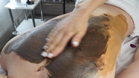 Female Masseur Hands Applies Chocolate Mask and Massages Back Relaxed Woman Footage