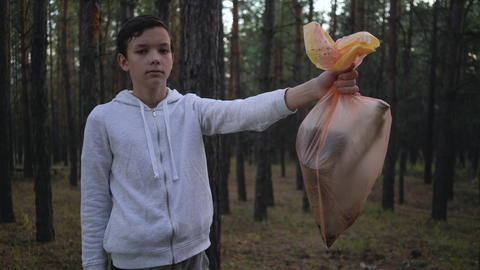 volunteer showing garbage bags after cleaning forest Live Action