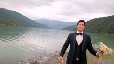 Happy groom tosses a bouquet near the river against the backdrop of majestic GIF