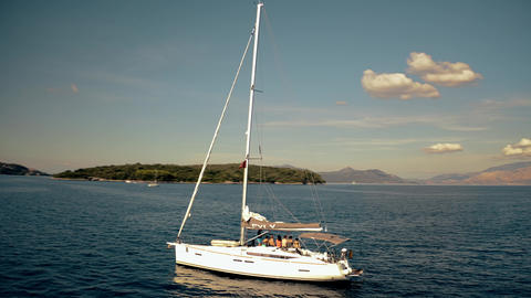 Aerial orbiting shot of unknown people relaxing on a sailing yacht at the Ionian Footage