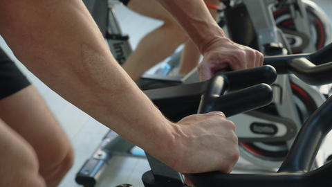 Male hands on handle indoor bike in fitness studio. Man spinning bike on cycling Live Action