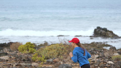 Woman runs along the stony shore of the ocean. Healthy active lifestyle. Slow Live Action