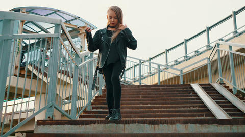 Teenager girl in black leather jacket walking down stairs on urban background Footage