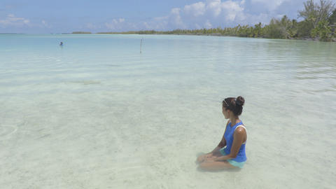 Polynesian beach - woman sitting by reef sharks in coral reef lagoon in Tahiti Live Action