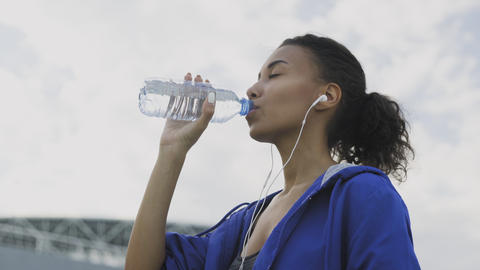 Afro-american runner woman Drinking Water After Running. Portrait Fitness Woman Footage