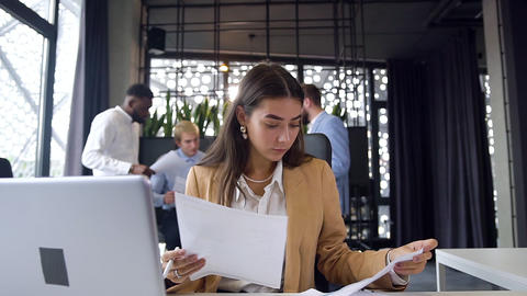 Attractive experienced young female office worker holding different reports and Footage