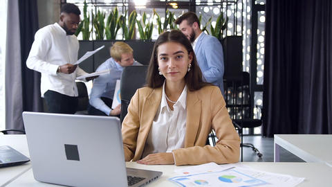 Pretty purposeful young businesswoman sitting at her workplace with computer and Footage
