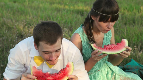 Young couple eating watermelon at picnic, closeup view Footage