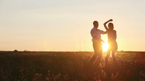Young couple silhouettes dancing on the field at sunset Stock Video Footage