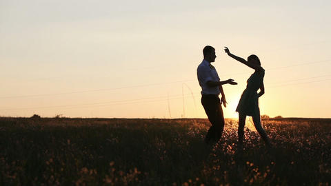 Young couple silhouettes dancing on the field at sunset Footage