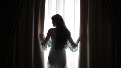 Young woman touches curtains in a bedroom against a warm morning light shining Live Action