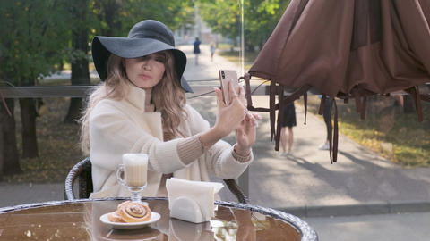 Beautiful lady takes a selfie with a smartphone posing in an outdoor cafe Footage