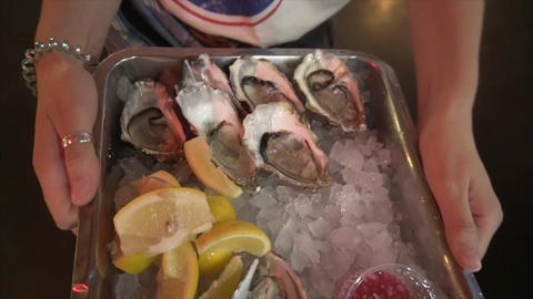 Gourmet dinner: fresh, delicious, high-quality oysters on a tray with ice, sauce Live Action