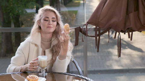 Elegant woman eating a sweet pastry cake in a street cafe Footage