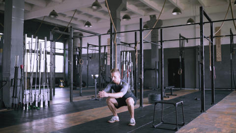 Male fitness instructor showing squat exercise at modern plase Footage