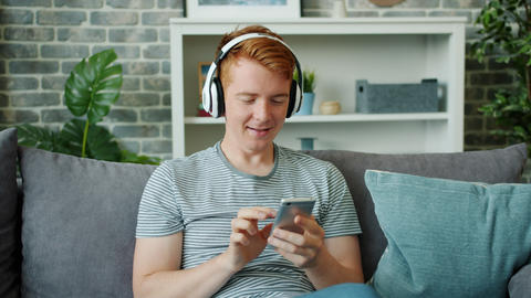 Joyful guy listening to music through headphones and using smartphone at home Footage