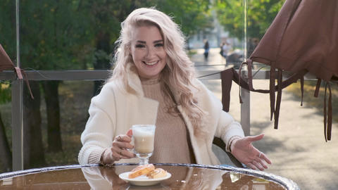 Beautiful lady is recording a video blog in an outdoor cafe Footage