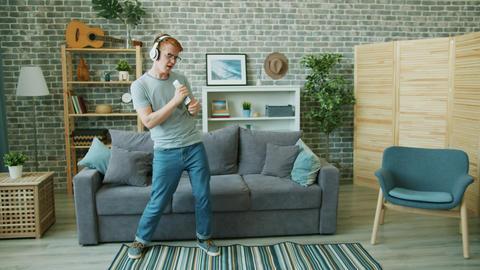 Joyful teenager in headphones dancing singing in remote control in apartment Footage