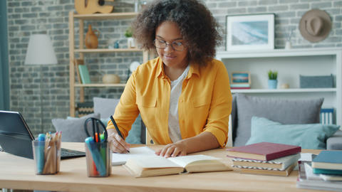 Smiling young woman writing in notebook at desk at home working at project Footage