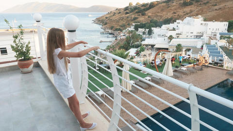 Teenager girl in white clothes standing on outdoor terrace at sea and swimming Footage