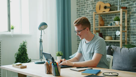 Happy teenager using laptop at desk at home typing enjoying communication Footage