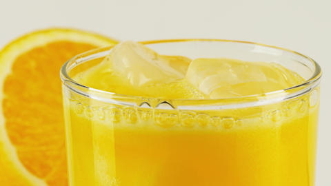 Carbonated orange soft drink with ice in a glass, close-up slow motion shot on Footage