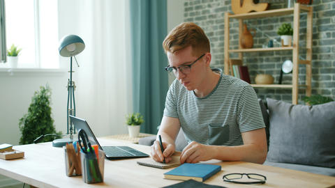 Male student studying at home using laptop typing then writing in notebook Footage