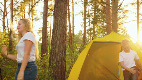 Tourist family waking up inside camping tent in sunny forest. Happy family on Footage