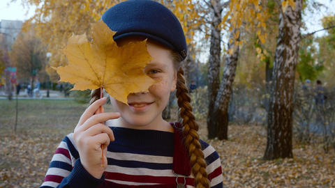 Portrait teenager girl with yellow maple leaf in hand near face. Smiling face Live Action