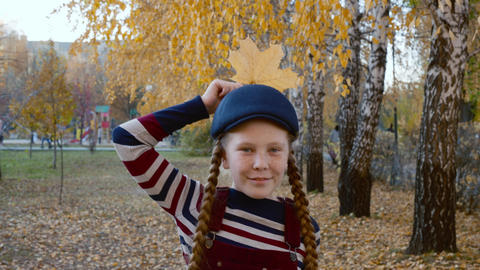 Girl teenager in striped clothes and blue cap with yellow maple leaf near head Footage