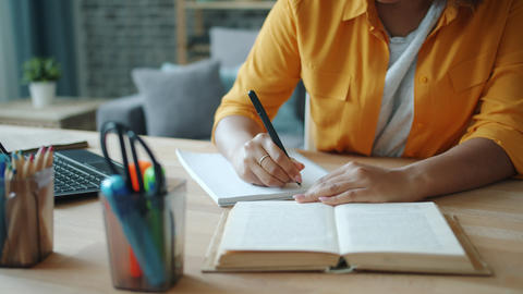 Close-up of female hand writing in notebook while woman reading book at table Footage