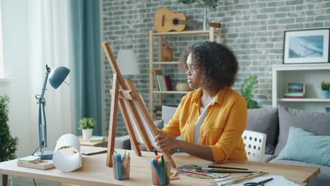 Teenage girl painting picture at home working alone using easel and pencil Footage