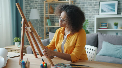 Beautiful African American girl painting at home with pencil and paints alone Footage