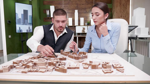 Young male and female architect working on a miniature town Footage