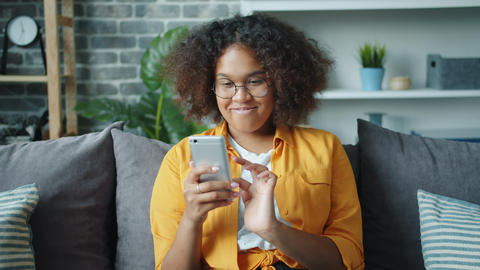 Beautiful African American girl using smartphone laughing relaxing at home Footage