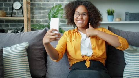 Happy Afro-American teenager taking selfie with thumbs-up hand gesture at home Footage