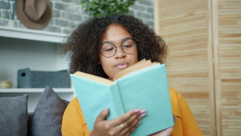 Pretty African American woman reading book at home turning pages smiling Footage