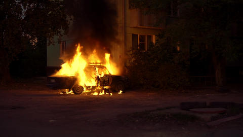 Burning car close to a house in a sleeping area of city Footage