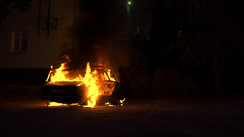 Car engulfed in flames of fire and burning at night Footage