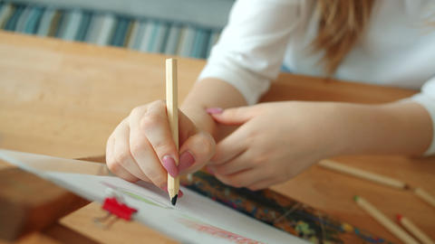 Close-up of female hand drawing picture on paper creating images with pencils Live Action