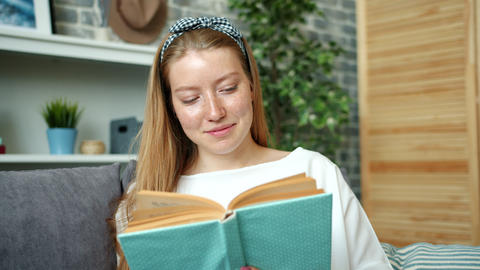 Portrait of attractive teenage girl reading book at home smiling turning pages Footage