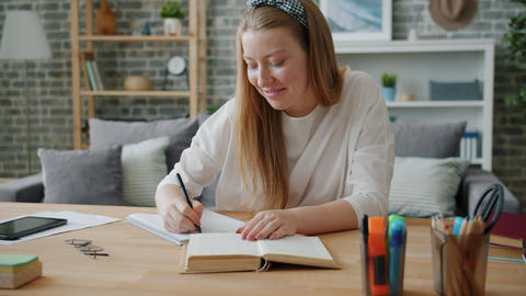 Young lady student writing in notebook at desk at home working at project Footage