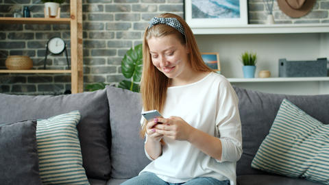 Beautiful blond girl using smartphone and laughing relaxing on couch at home Footage