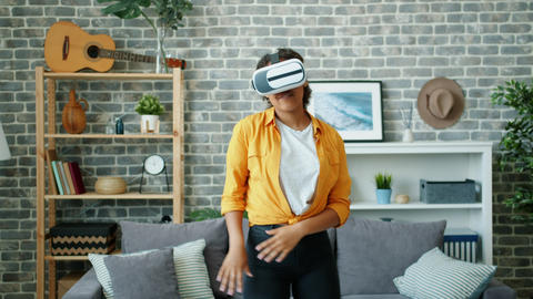 Happy African American woman dancing in virtual reality glasses at home Footage