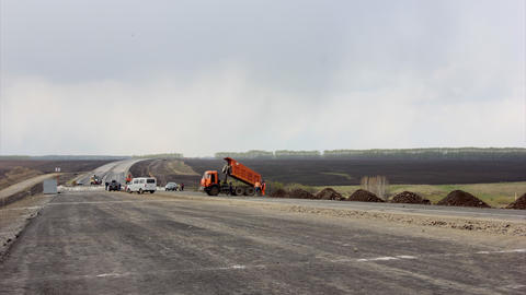 Timelapse Road construction trucks pour graph and sand Footage