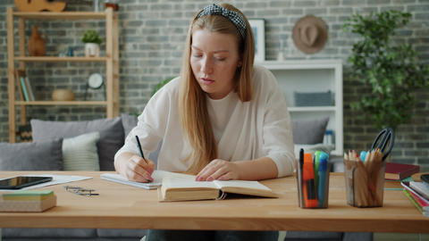 Smart young lady working at project at home writing reading book at desk Footage