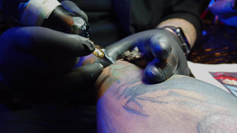 Transferring ink under the skin at a tattoo studio - close up view over a Footage