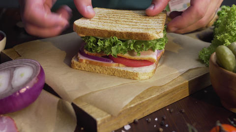 Chef finalizes the sandwich with leaf of green fresh salad on the wooden board Live Action